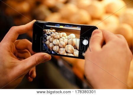 Cropped picture of man make photo of a lot of bread and pastries in supermarket bakery by his phone