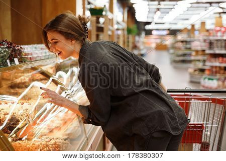 Photo of smiling young lady standing in supermarket choosing pastries. Looking aside.