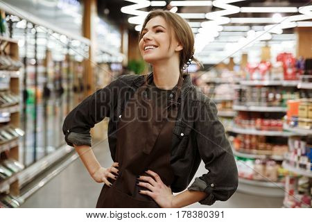 Picture of cheerful young lady in supermarket standing and posing. Looking aside.