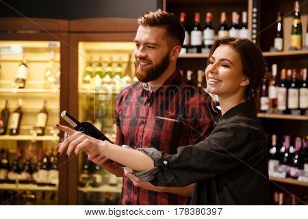 Image of young concentrated happy loving couple in supermarket choosing alcohol. Looking aside.