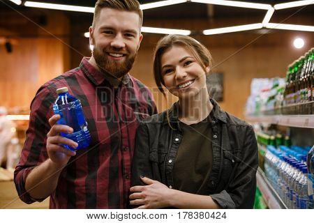Photo of young happy loving couple in supermarket choosing water. Looking at camera.
