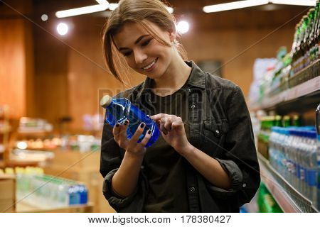Photo of young concentrated cheerful lady in supermarket choosing water. Looking aside.