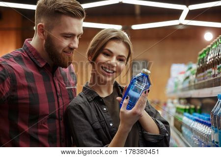 Image of young cheerful loving couple in supermarket choosing water. Looking aside.