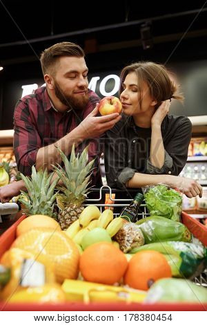 Picture of cheerful young loving couple in supermarket with shopping trolley choosing and smelling fruits. Eyes closed.