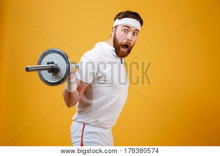 Portrait of an excited bearded fitness man workout with barbell isolated on a white background
