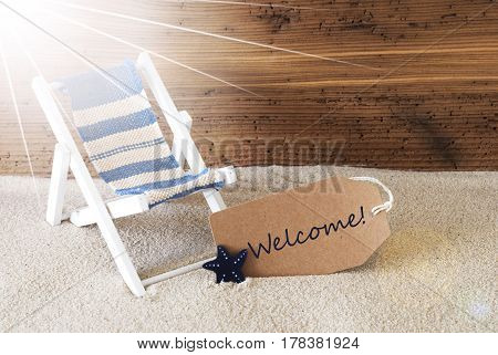 Sunny Summer Label With Sand And Aged Wooden Background. English Text Welcome. Deck Chair For Holiday Or Vacation Feeling.