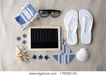 Flat Lay Of Blackboard On Sandy Background. Summer Decoration As Holiday Greeting Card. Sand And Beach Environment. Copy Space For Advertisement Or Free Text