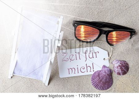 Sunny Summer Label With German Text Zeit Fuer Mich Means Time For Me. Flat Lay View. Summer Decoration With Deck Chair, Seashells And Sunglasses. Greeting Crad With Sand Background