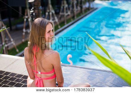 Enjoying suntan. Pretty young woman in bikini sitting near swimming pool