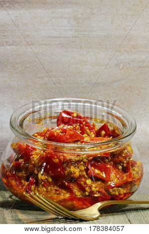 A jar of red chili pickle marinated in mustard seeds and mustard oil and Indian pickling spices