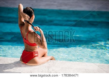 Beautiful dark hair sexy woman young girl model in sunglasses and elegant red sexy swimsuit lingerie with crystals around the pool.