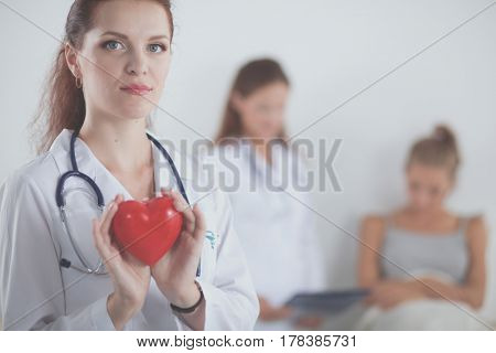 Young woman doctor holding a red heart, standing