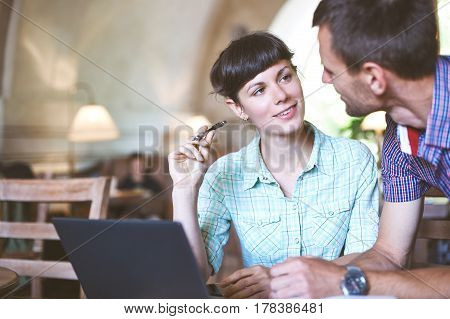 Man and woman are sitting together at the table in the office and both are Look at each other. On the desk is a laptop and papers, documents. Concept of business or education
