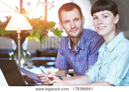 Man and woman are sitting together at the table in the office and both are looking at the camera. On the desk is a laptop and papers, documents. Concept of business or education