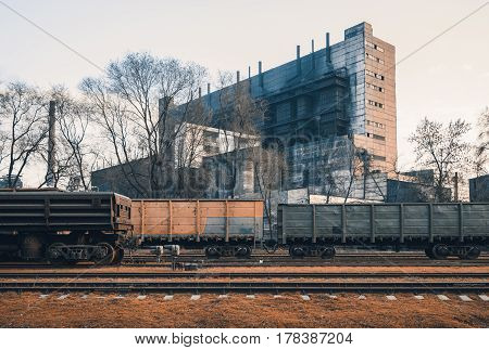 Railway station with freight wagons and train against metallurgical plant at sunset. Colorful industrial landscape. Railroad with vintage toning. Railway platform. Heavy industry. Cargo shipping