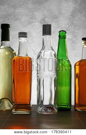Different bottles of wine and spirits on color background