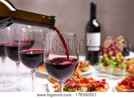 Pouring red wine into glass at lunch time