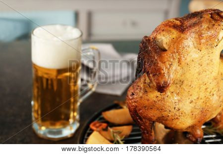 Grilled beer can chicken on kitchen table