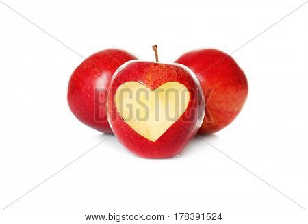 Fresh red apples and one with heart-shaped cut out on white background