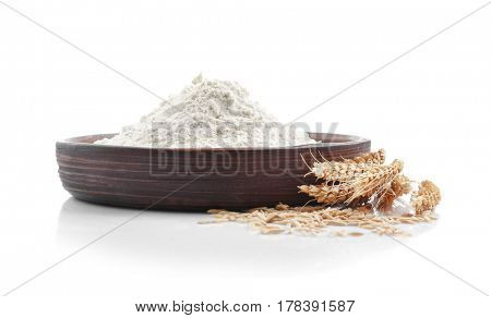 Bowl with flour and spikelets on white background