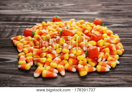 Tasty Halloween candies on wooden background, closeup