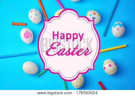 Text HAPPY EASTER with painted eggs and felt tip pens on color background