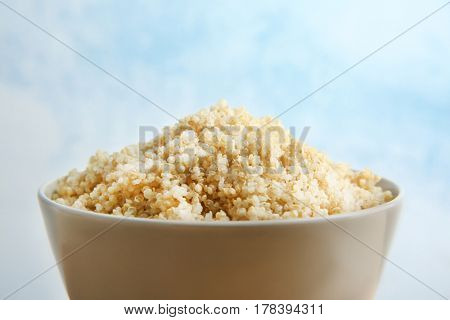 Ceramic bowl with boiled sprouted organic white quinoa grains, closeup