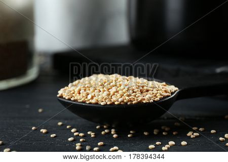Spoon with quinoa seeds on dark table