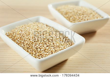 Bowls with quinoa seeds on wooden table