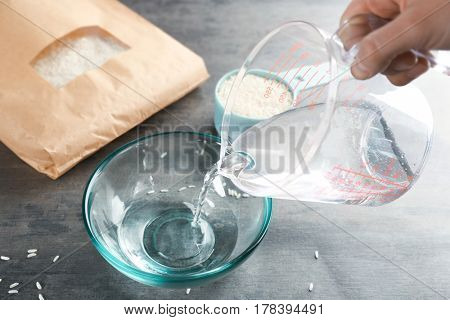Cooking concept. Pouring water into glass bowl