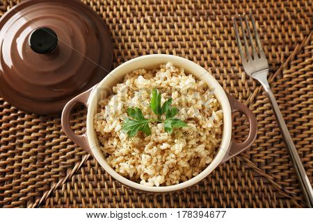 Bowl with brown rice on wicker mat background