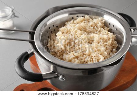 Colander with prepared rice in saucepan