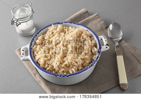 Bowl with brown rice on gray table