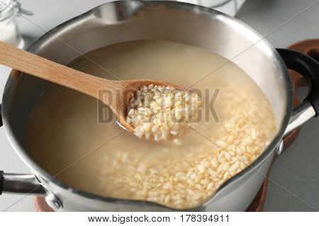 Spoon with brown rice in saucepan on table