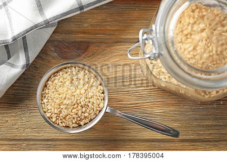 Metal measuring cup with brown short grain rice on wooden table