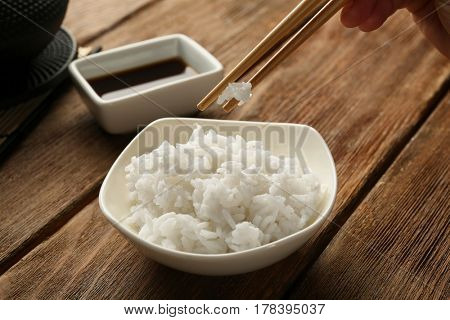 Woman eating rice with chopsticks on wooden table