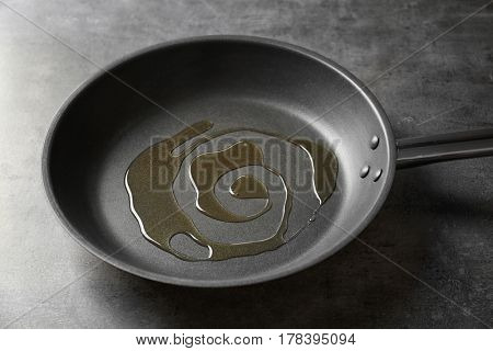 Pan with oil on gray background