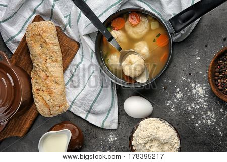 Stewpan with delicious chicken and dumplings on kitchen table
