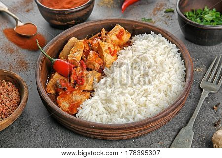 Chicken tikka masala with rice in wooden bowl and ingredients on table