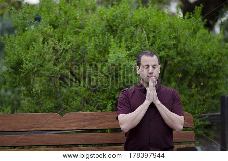 Man praying on a bench with his hands together.