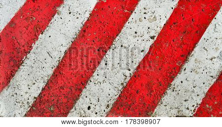 Diagonal red-white lines paint pattern on a rough textured cement