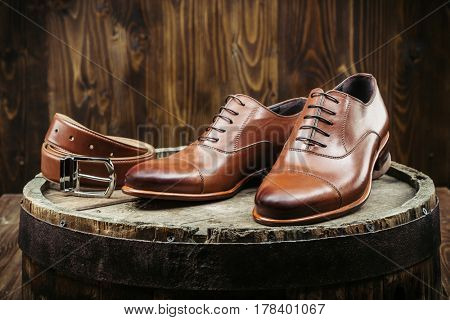 Stylish men's shoes and belt on a wooden table on a dark wooden background