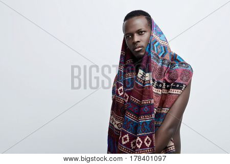 Close up shot of attractive dark-skinned male with clean healthy skin wearing colourful etnic blanket or scaff looking serious and thoughtful. Pensive hipster young black man posing indoors in studio looking aside