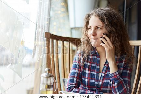 Young charming woman calling cell telephone while sitting alone in coffee shop during free time. Doubtful and indecisive she is looking at the window with thoughtful pensive expression pursuring her lips waiting for her lunch to be ready.
