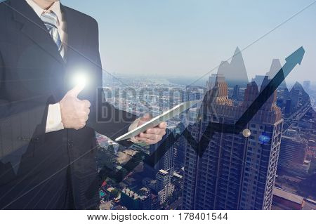 Double Exposure Of Businessman Using Tablet And Give Thumbs Up On Financial Graph Chart And Building