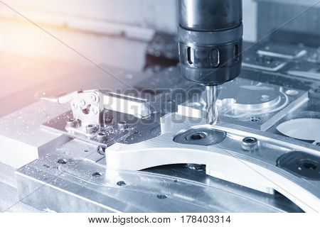The CNC milling machine cutting the sample part with the cutting tool in light blue scene and lighting effect