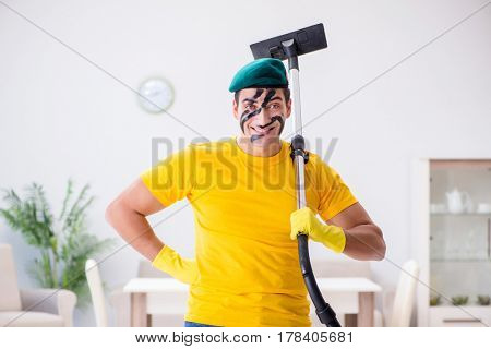 Funny man in military style cleaning the house