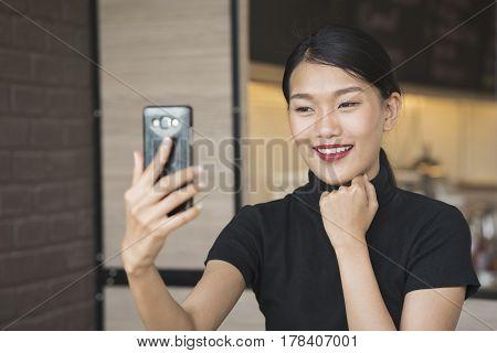 portrait of asian woman take selfie using smart phone camera