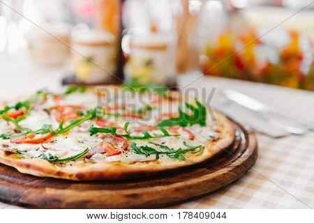 Pizza with cheese, tomato and meat, on served table with plaid tablecloth