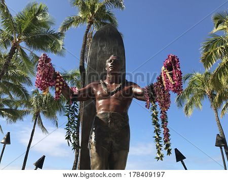 WAIKIKI, HI - March 15, 2017. A photo of the famous Duke Kahanamoku Statue on Waikiki Beach in Honolulu, Hawaii. The Duke is a legendary figure who popularized the sport of surfing and won gold medals for the USA in swimming.